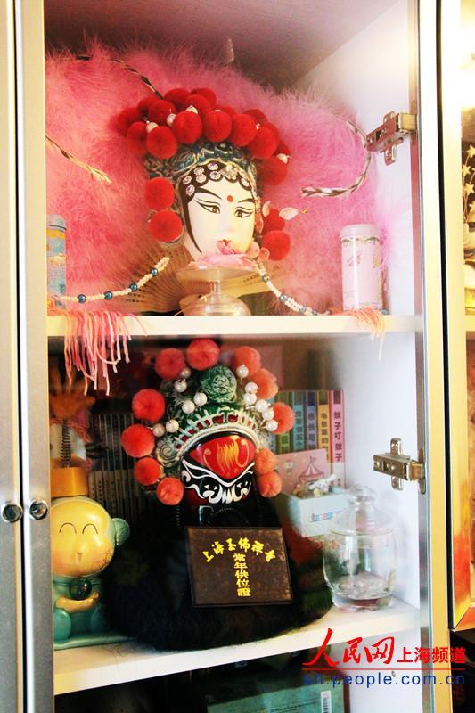 柜子里,可爱的卡通娃娃与两个浓墨重彩的戏剧脸谱