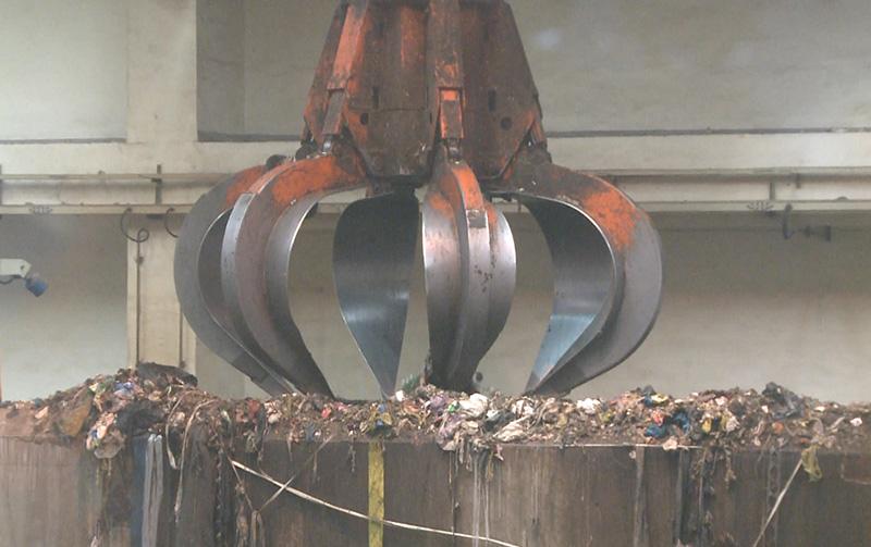 工作人员通过机器设备,将垃圾加入到焚烧炉中