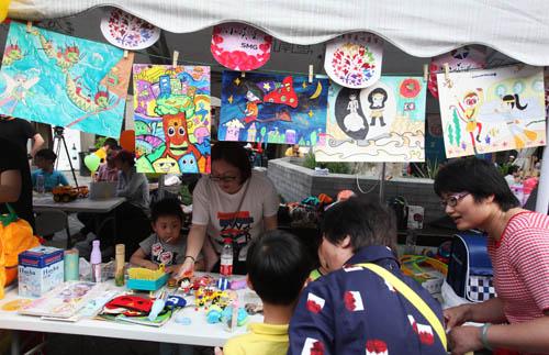 """第四届""""荧星杯""""儿童绘画大赛60幅获奖绘画作品也在爱心集市义卖."""