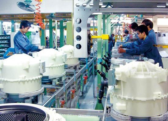 图:小天鹅滚筒洗衣机内桶生产线上,工人正在辛勤工作